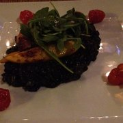 "Squid ink ""risotto"" with squid and octopus confit, cherry tomatoes, baked mango and rocket"