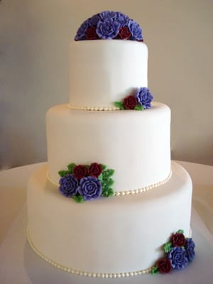 Simple and elegant wedding cake with dusty burgundy and violet roses