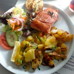 Grilled salmon with side salad, potatoes and garlic bread