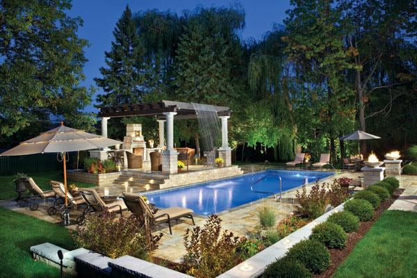 rectangle pool with arbor over patio and beautiful landscaping
