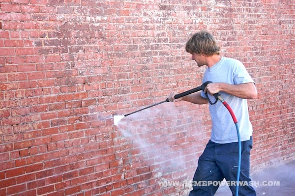 Power Washing Red Brick Of A Building Exterior In Downtown
